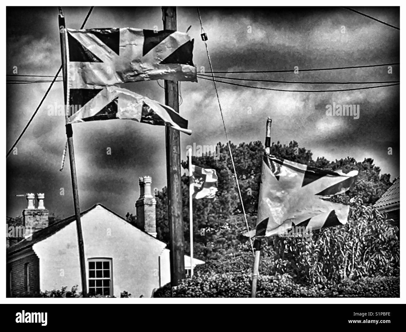 Weather Beaten Union Flags. - Stock Image