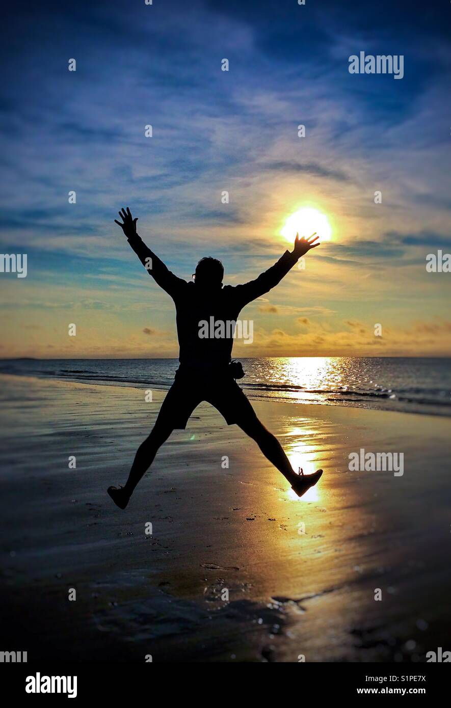The silhouette of a man jumping high in the air on a sunlit beach at sunset with the ocean behind. - Stock Image