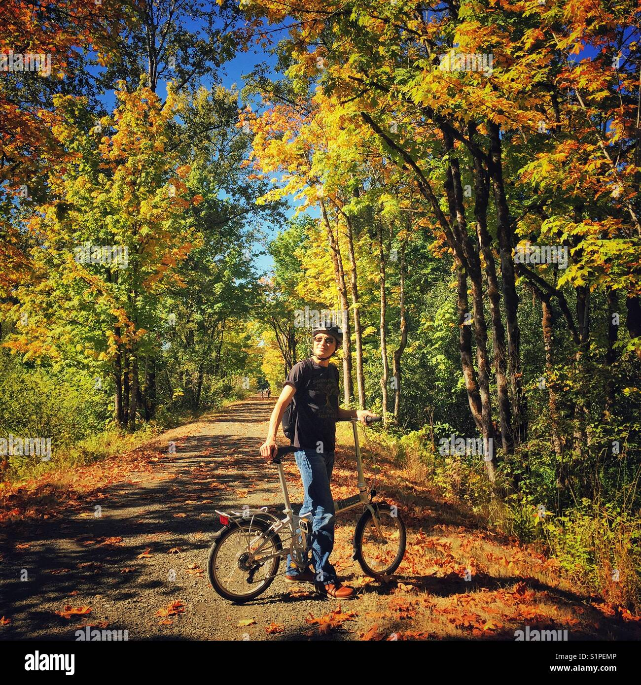 Man stops to rest on a bike trail on a sunny day surrounded by fall foliage on a sunny day - Stock Image