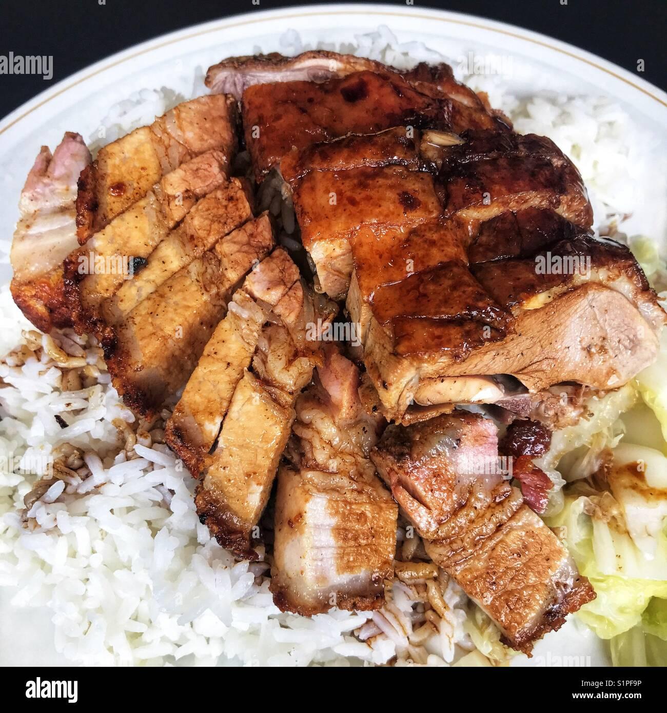 Cantonese roast duck and crispy pork belly rice - Stock Image