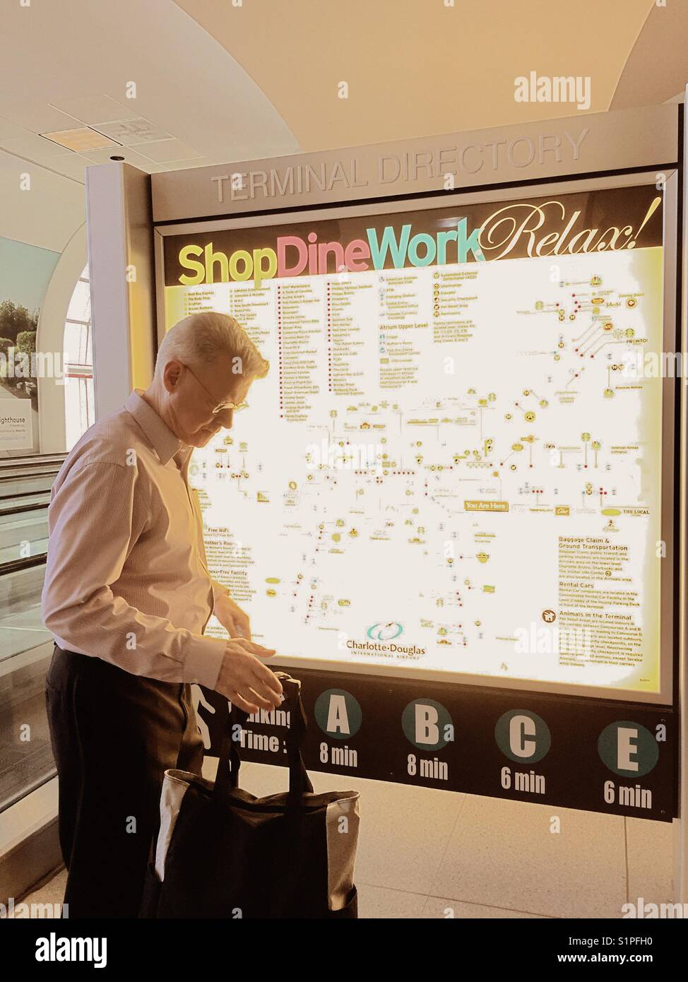 Senior male traveler looking at brightly lit airport terminal map ...