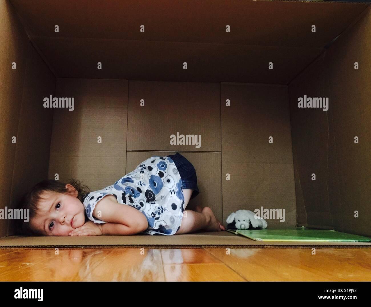 Sad toddler girl in a cardboard box - Stock Image