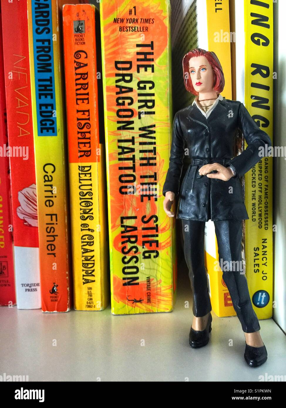 A toy figure of Dana Scully (Gillian Anderson) from the X Files standing near feminist themed books with orange - Stock Image