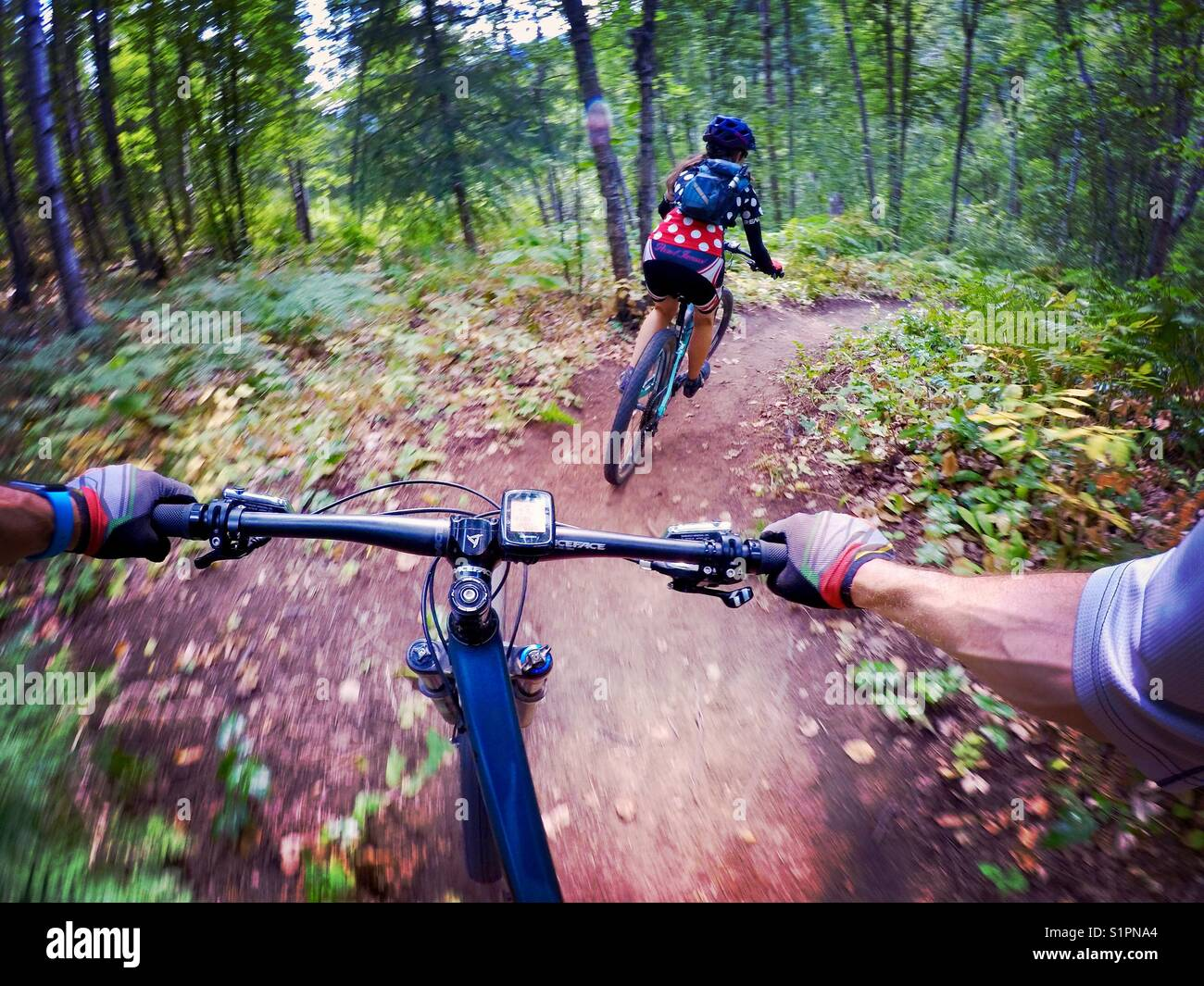 A male and female mountain biker speed down a trail with the female leading the pack - Stock Image