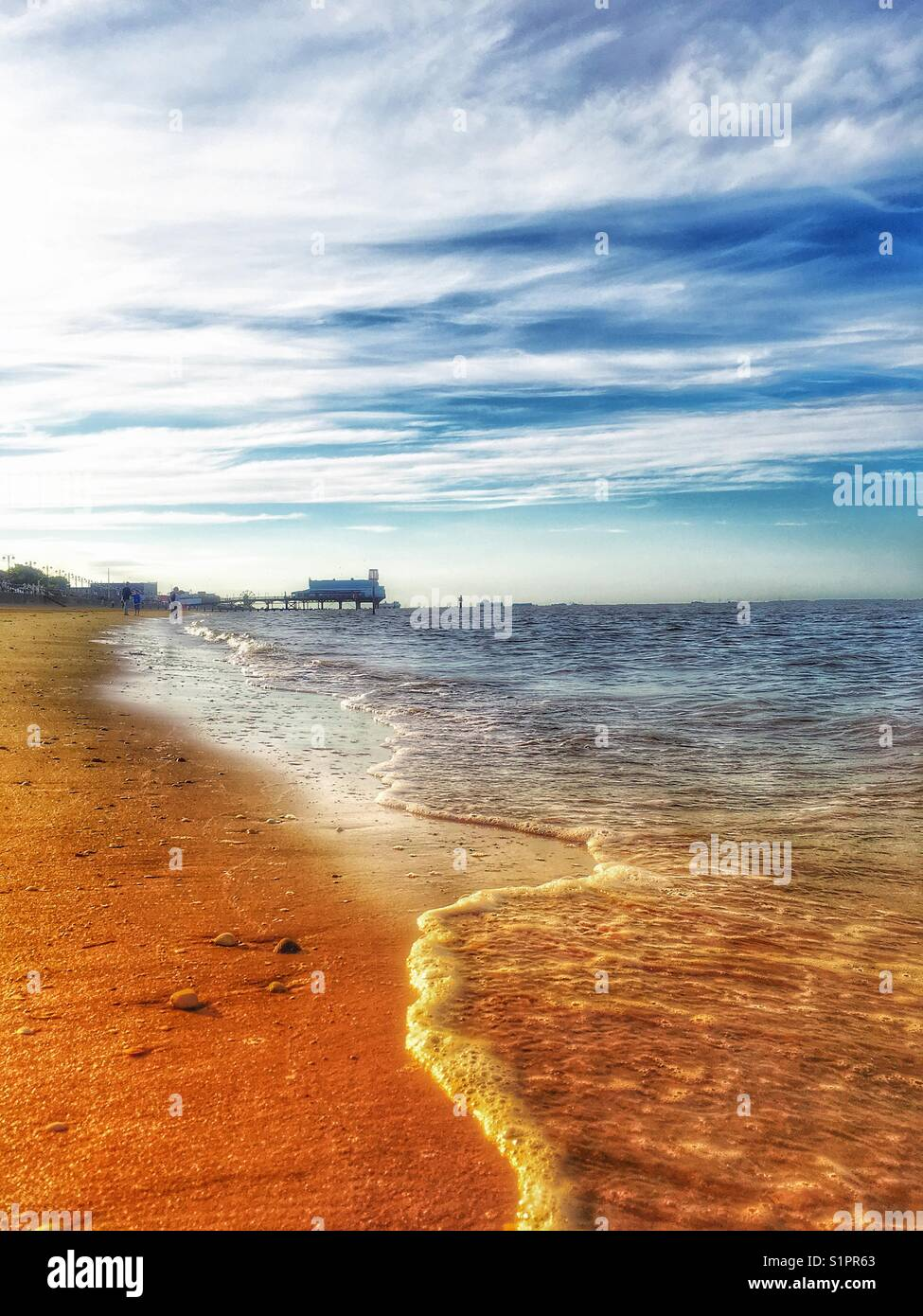 Surf along the beach at Cleethorpes UK at sunset. - Stock Image