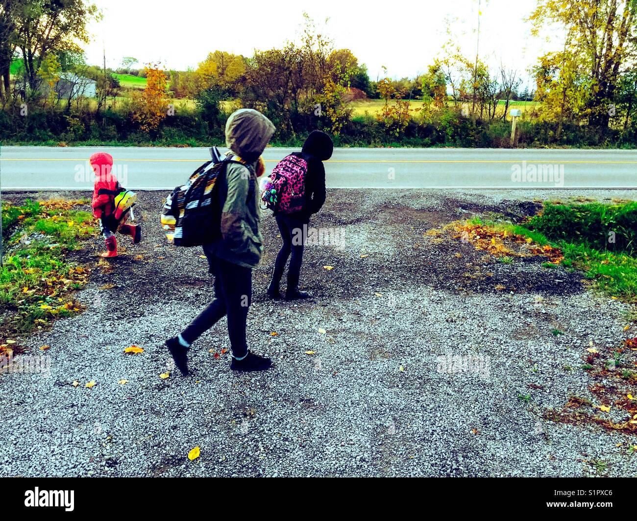 Three girls waiting for bus at bottom of rural driveway in Ontario, Canada - Stock Image