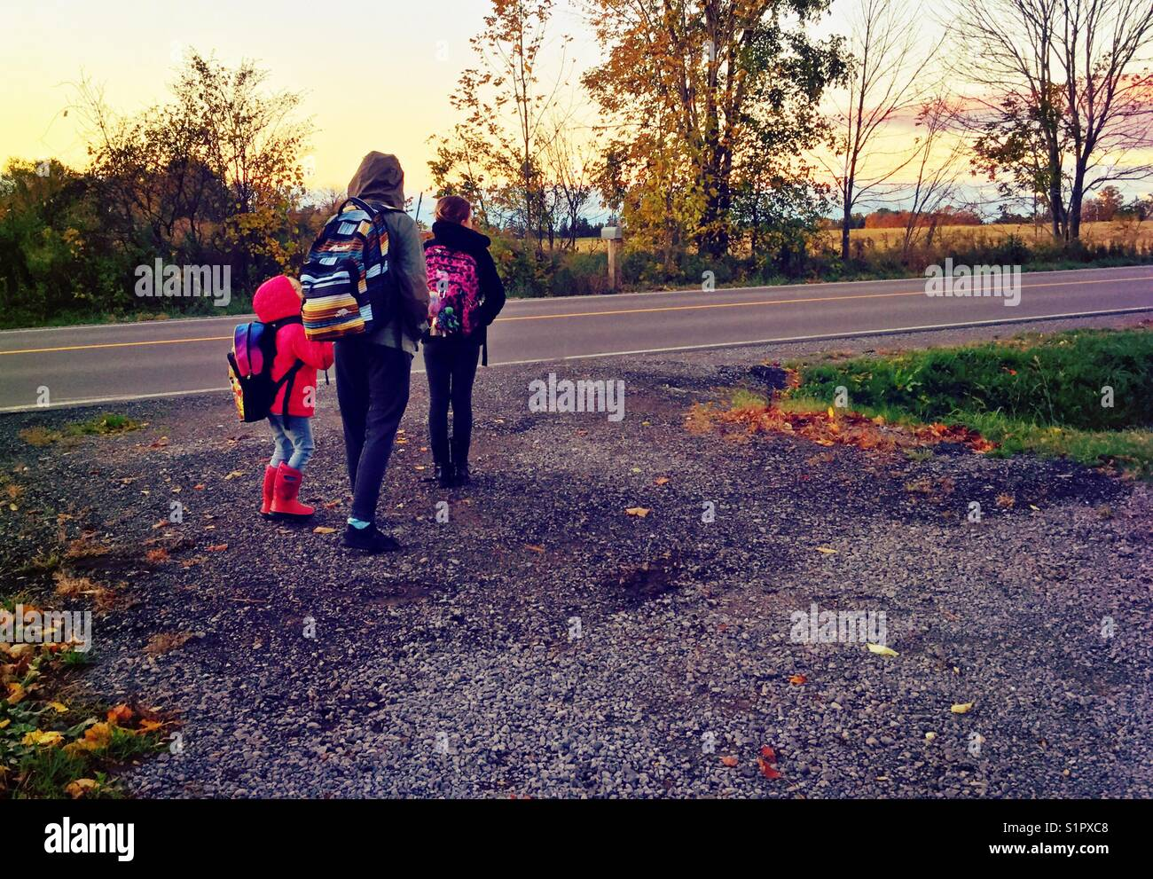 Three girls waiting for school bus at bottom of driveway in rural Ontario, Canada - Stock Image