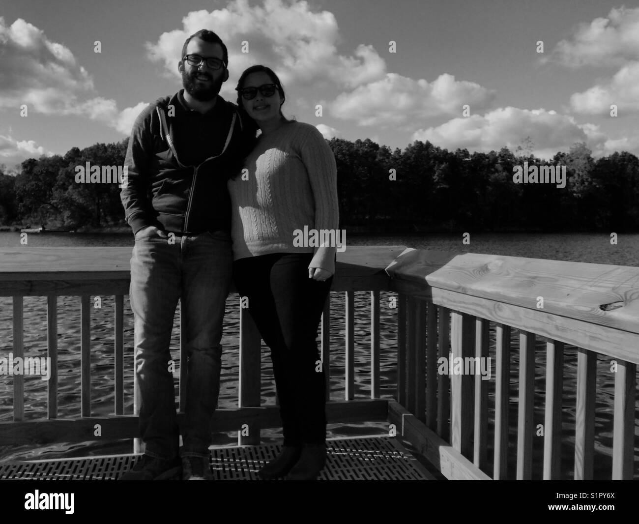 Husband and wife on a pier by the lake posing for couple photos - Stock Image