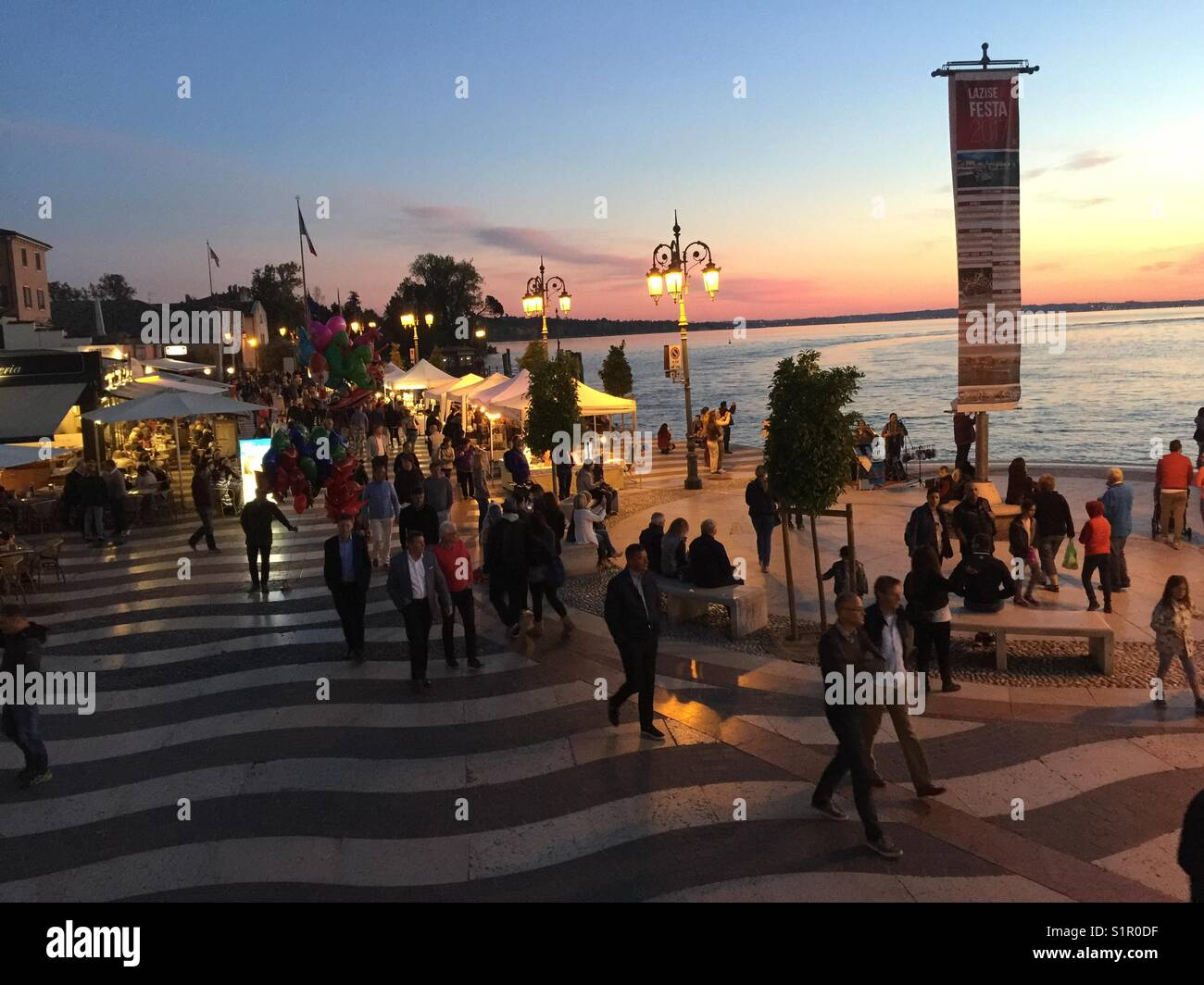 via Sponchi, Lazise Venezia, Italy, lake side or board walk in harbour with pedestrians , tourists and cafes under - Stock Image