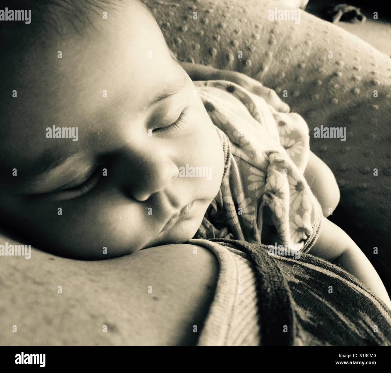 Newborn baby girl sleeping on mother's shoulder Stock Photo