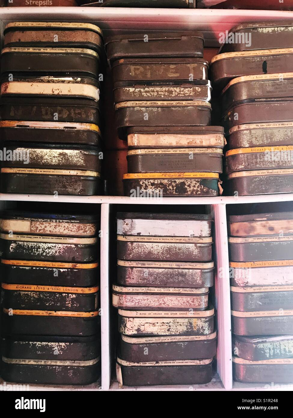 Rusty old vintage tins stacked up on shelves, UK - Stock Image