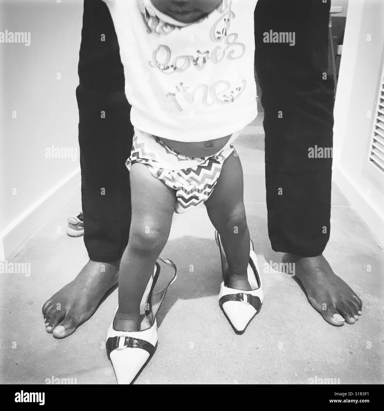 Baby walking in mommy shoes - Stock Image