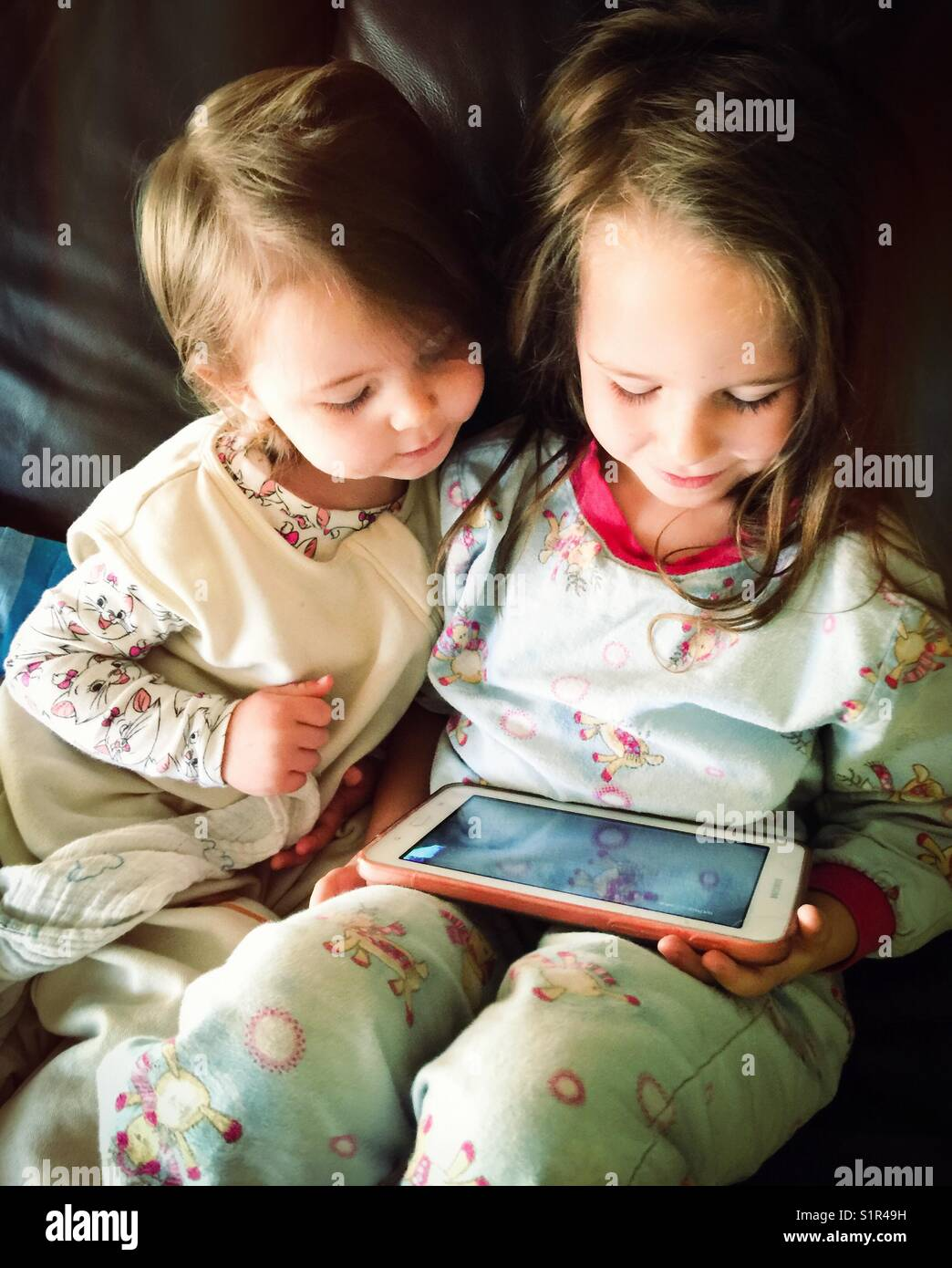 Young sisters watching videos on a tablet - Stock Image