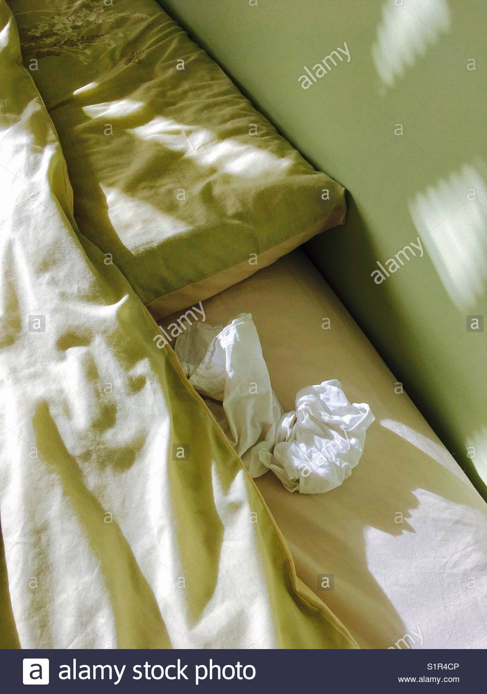 Crumpled pillow and bed sheets with crumpled handkerchief - Stock Image