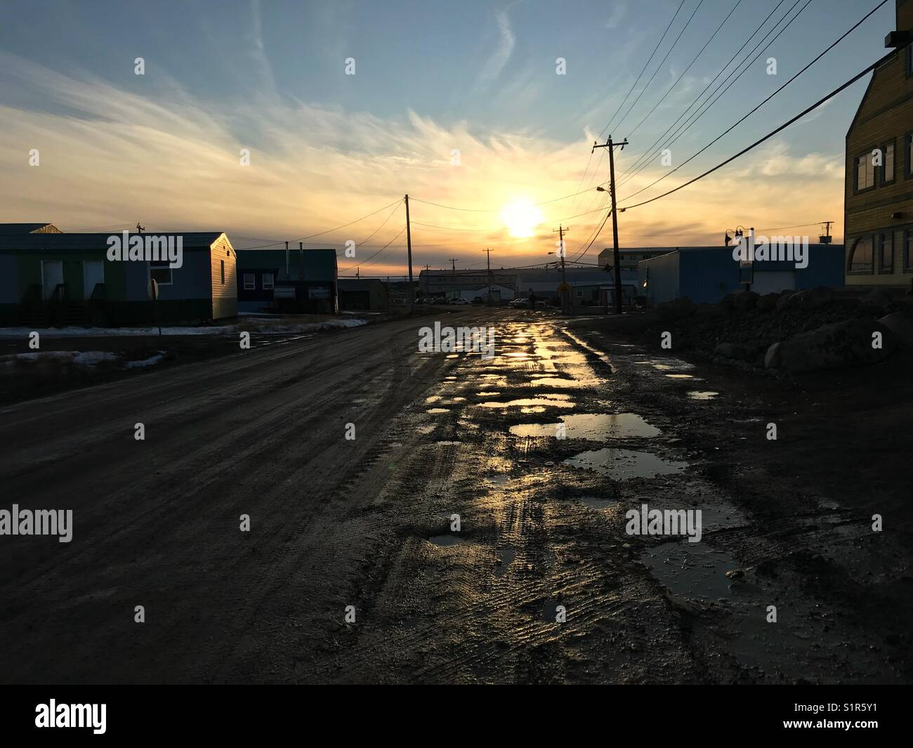 Sunset shine on potholes on dirt road, Iqaluit, Nunavut, Canada - Stock Image