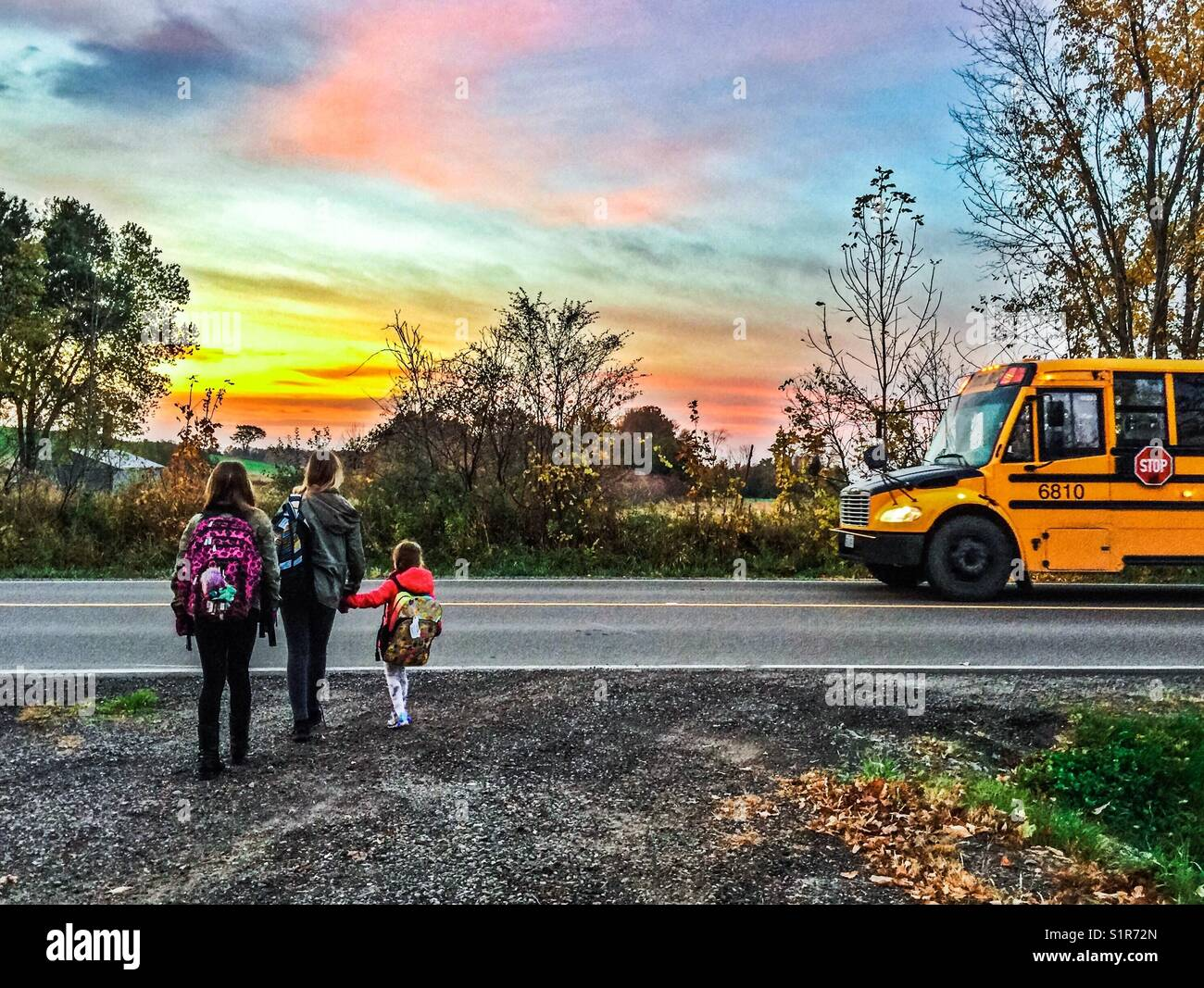 Three girls about to get on school bus in rural Ontario, Canada - Stock Image