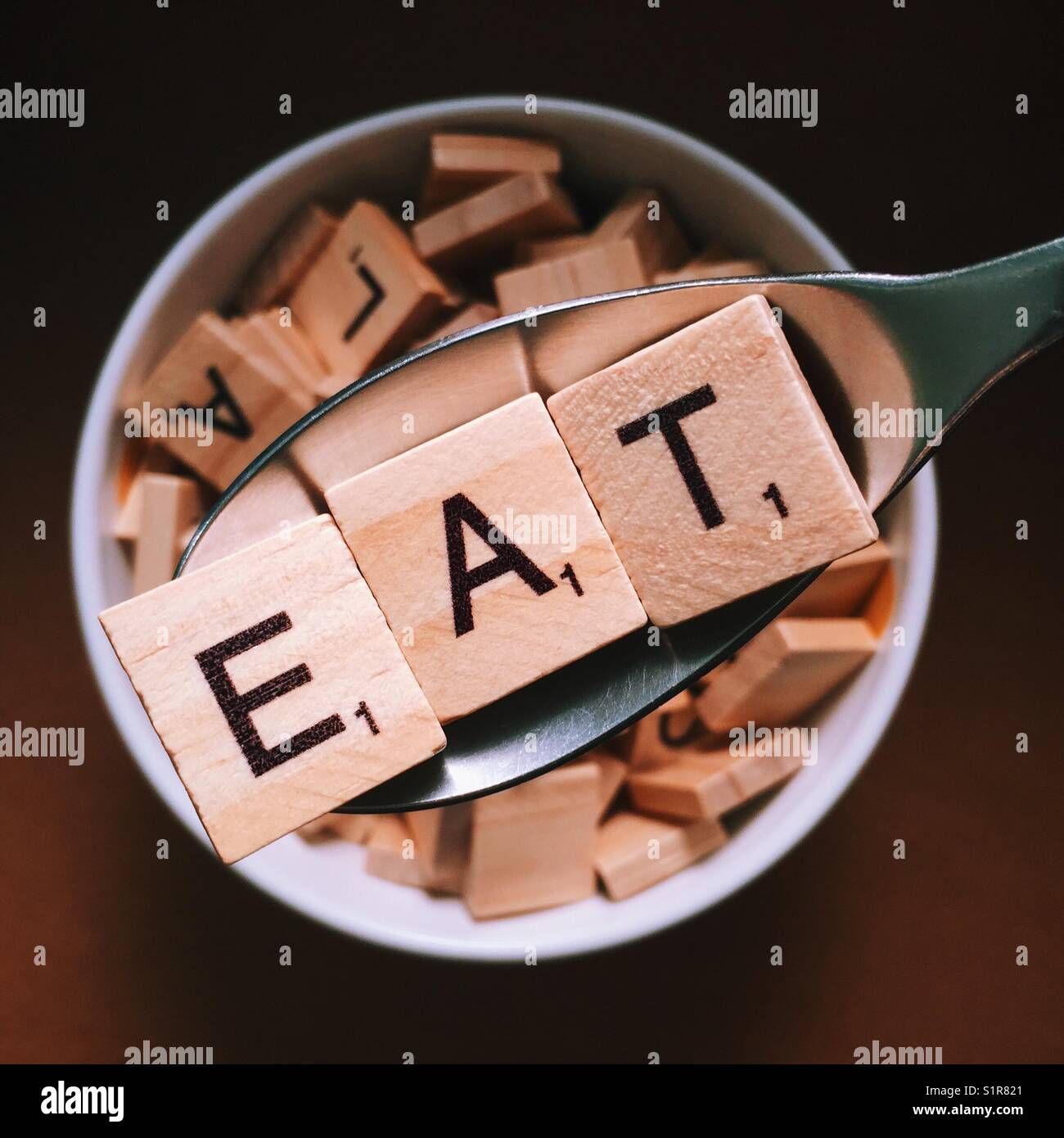 Close up of a spoon with wooden letters on it spelling eat and a bowl full of wooden letters beneath it - Stock Image