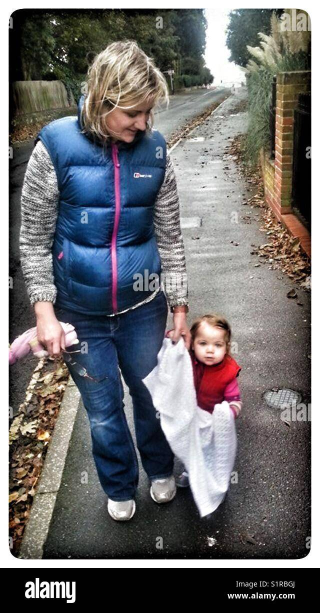 One year old taking a walk with her comfort blanket. - Stock Image