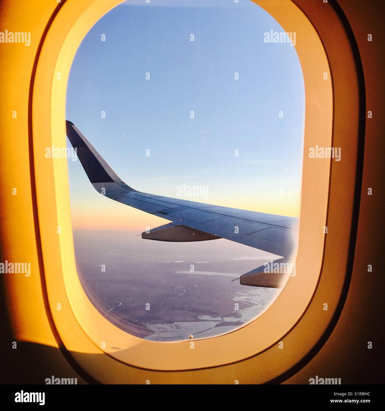 Airplane wing through the window at sunrise - Stock Image