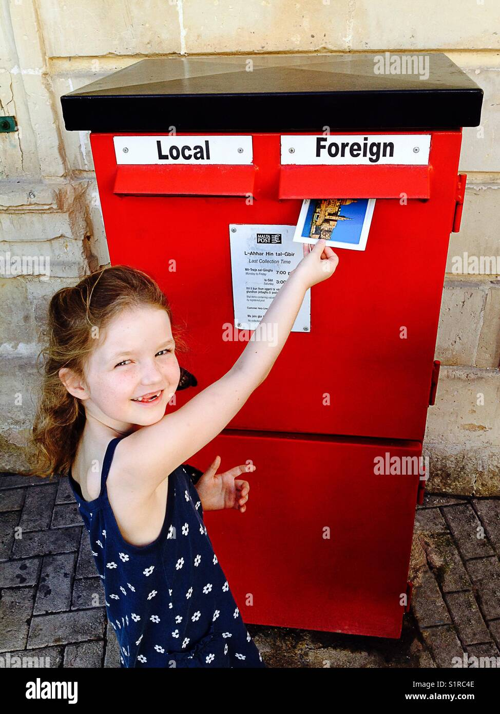 Child/ kid /girl posting a postcard into a letterbox with a Foreign destination marked slot. Malta. - Stock Image