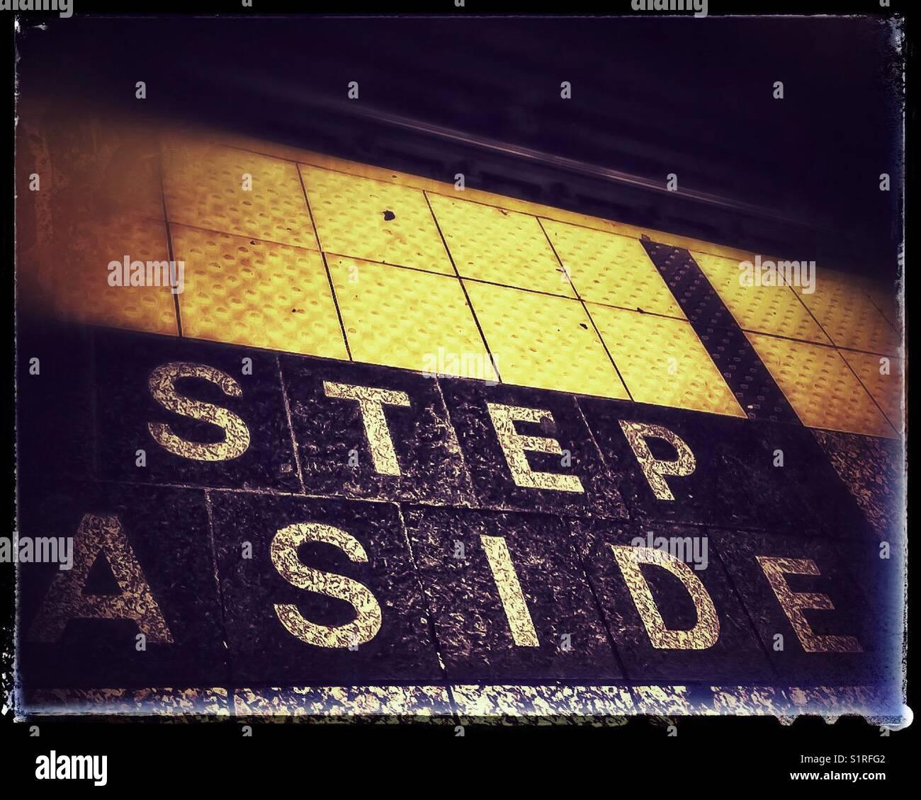 Step Aside written on subway platform - Stock Image