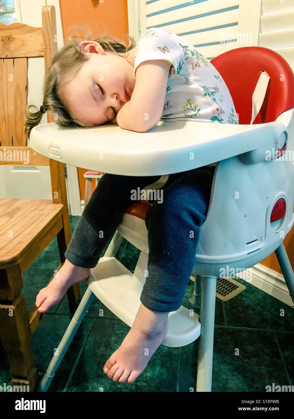 Toddler Girl Asleep In Her High Chair At Dinner