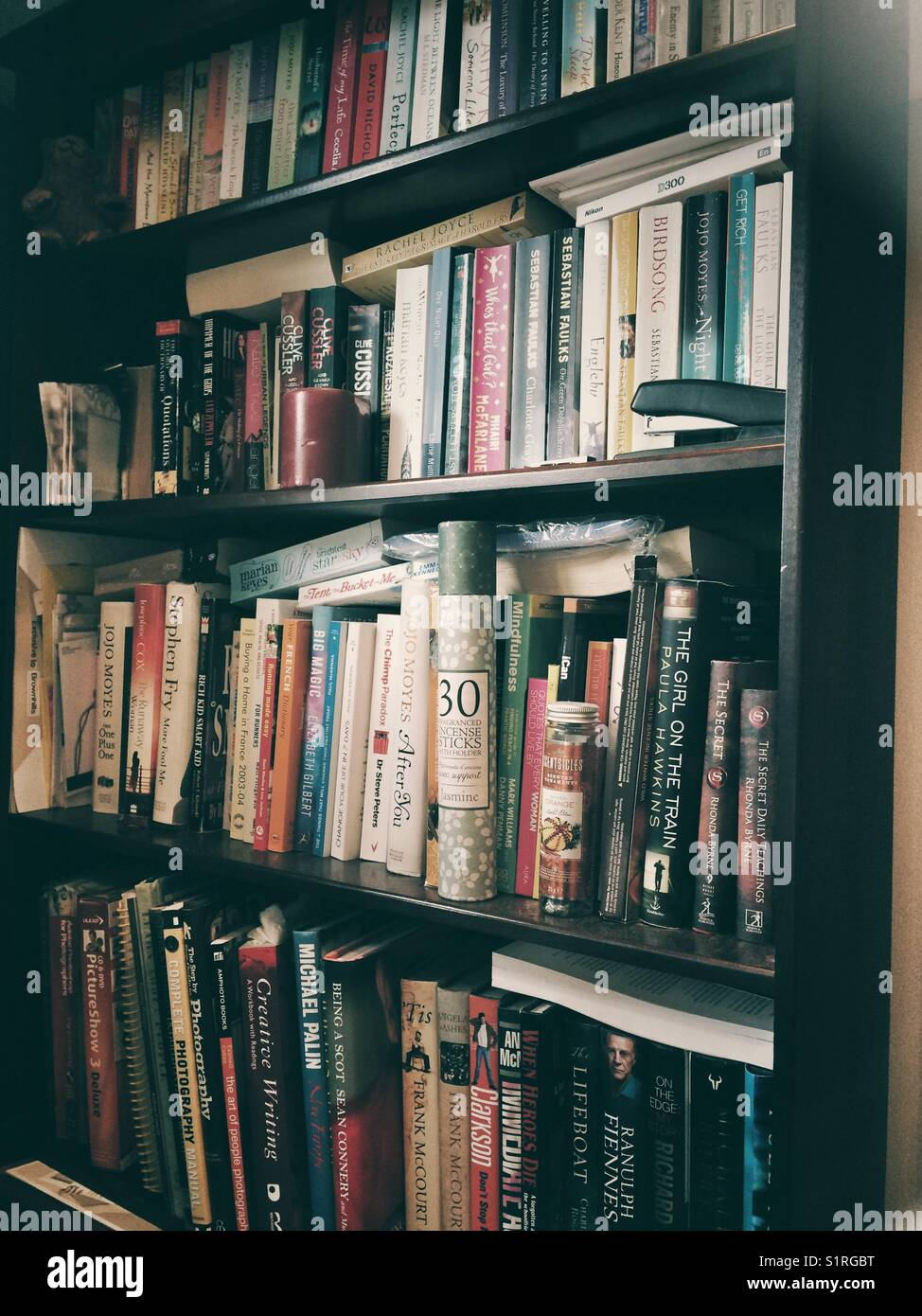 Cluttered book shelves - Stock Image