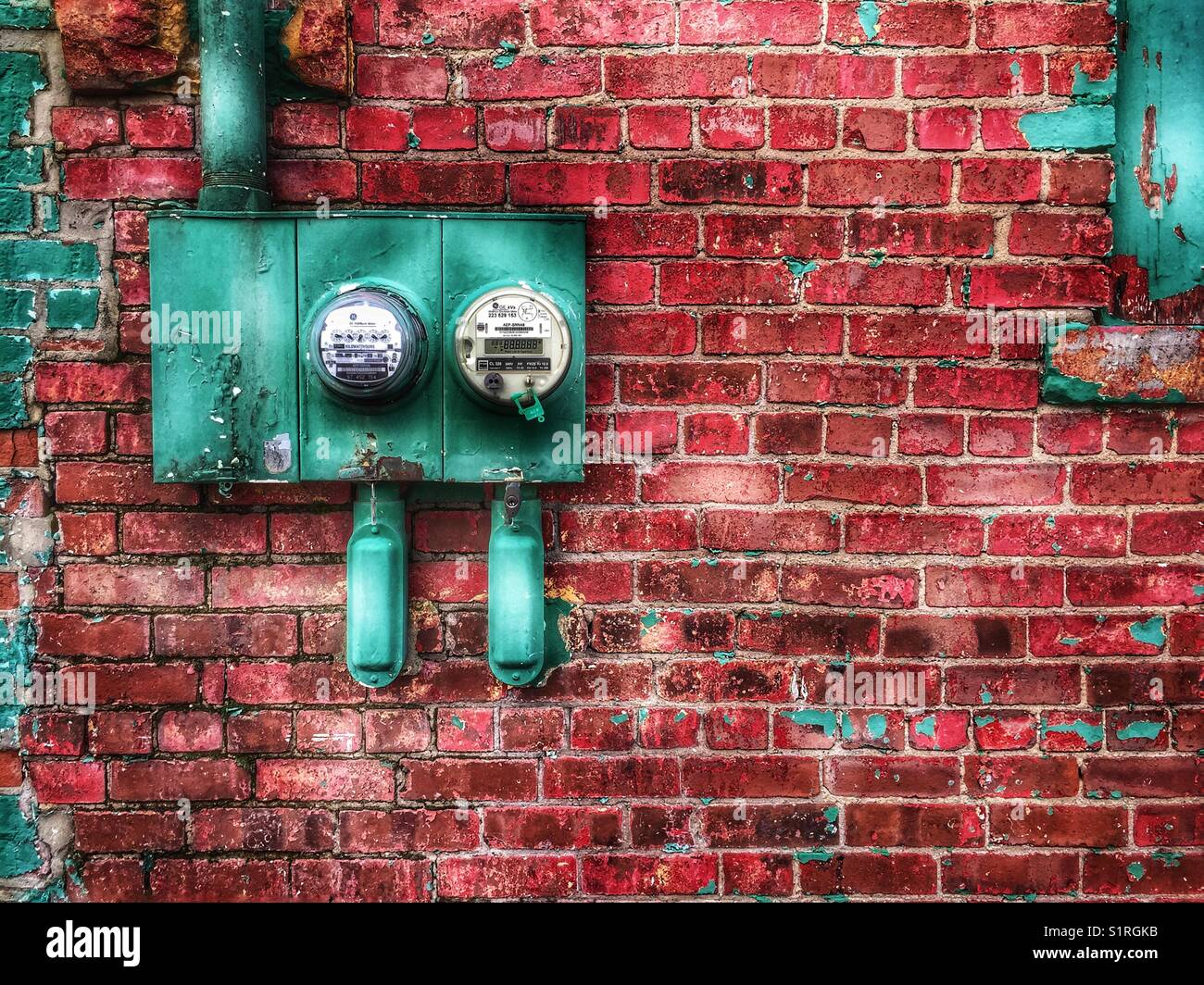 Red brick wall with electric meter - Stock Image