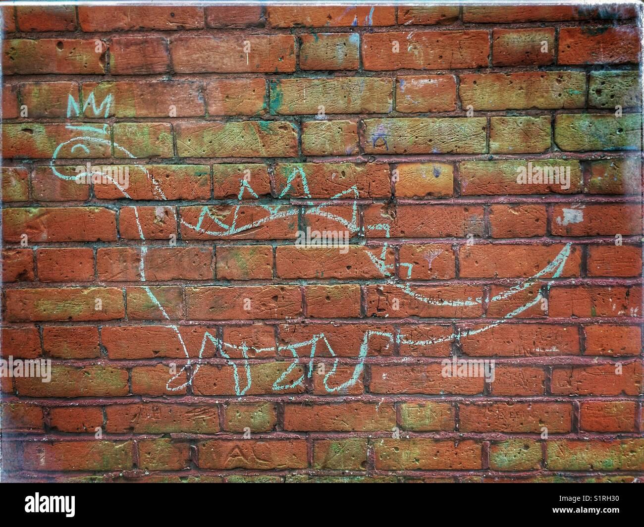 Chalk drawing of a brontosaurus dinosaur on a brick wall - Stock Image