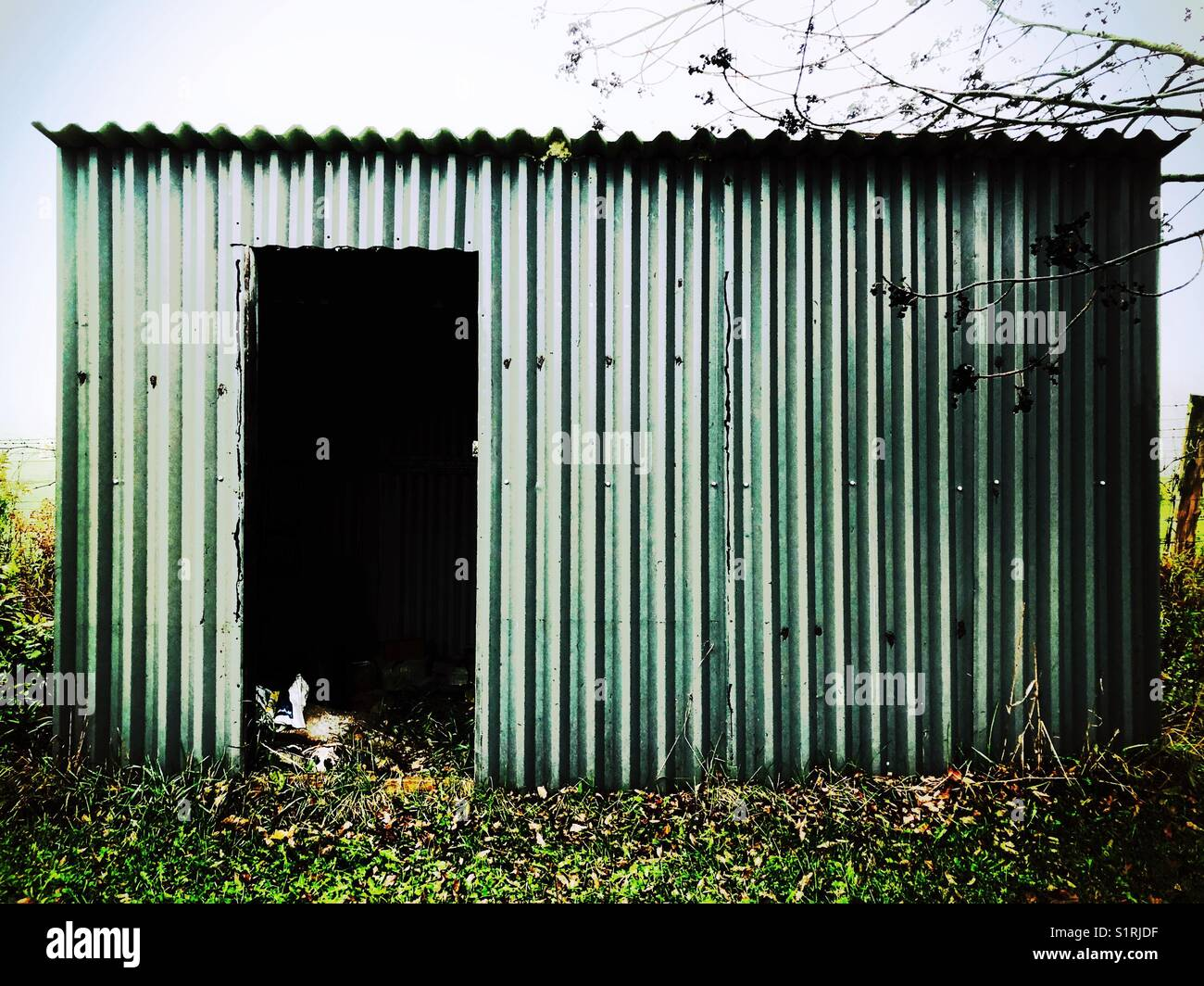 Creepy old metal shack with no door full of junk - Stock Image