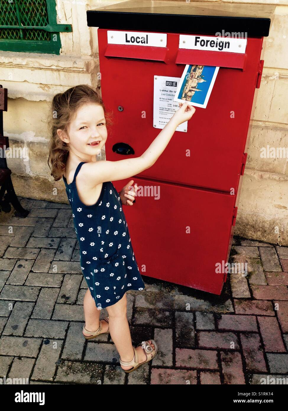 Young girl / kid / child posts her postcard into a letterbox / red letter box / mail box through the slot marked - Stock Image