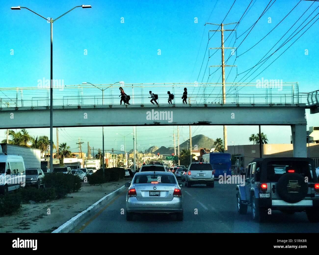 School children running across a bridge over a busy street in Cabo San Lucas, Mexico. - Stock Image