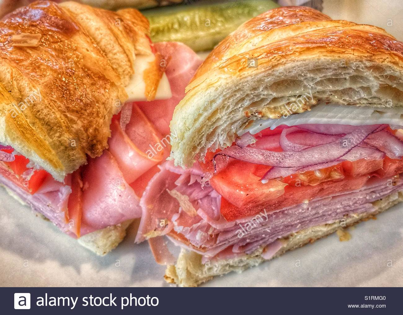 Ham and Swiss cheese on a croissant with mustard tomatoes and red onions sliced in half on a plate - Stock Image