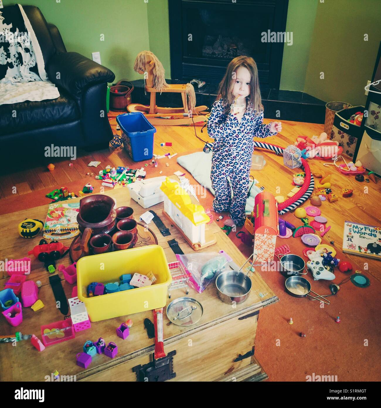 Young girl looking innocent amidst the huge mess of toys she made - Stock Image