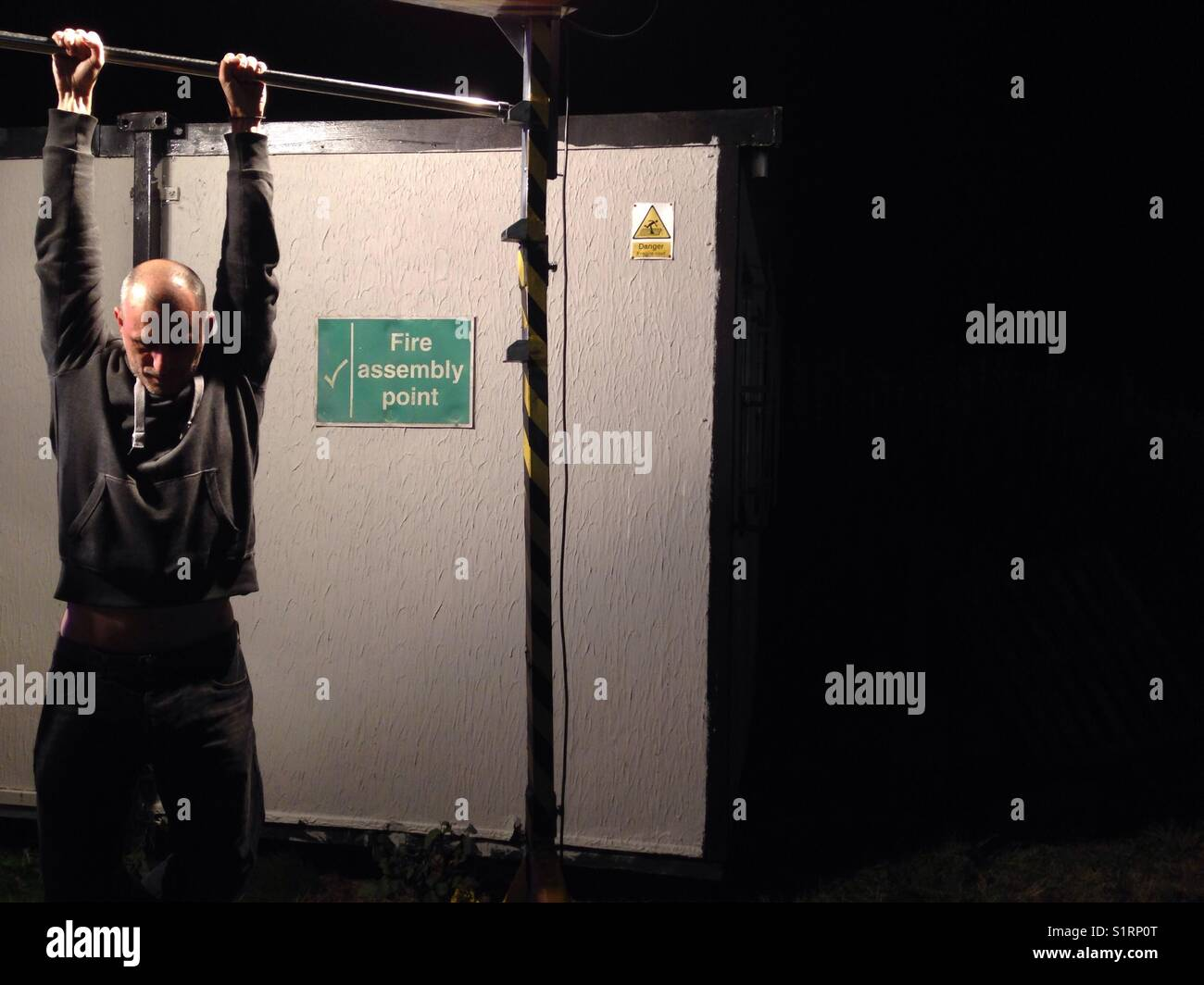 Man hanging from a bar at night - Stock Image