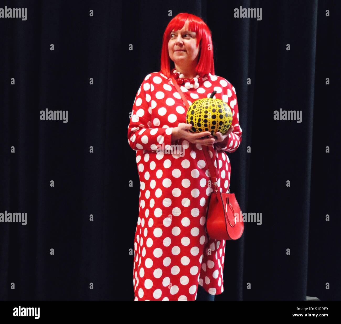 Middle aged Caucasian woman dressed as Japanese artist Yayoi Kusama holding dotted pumpkin for  American Halloween - Stock Image