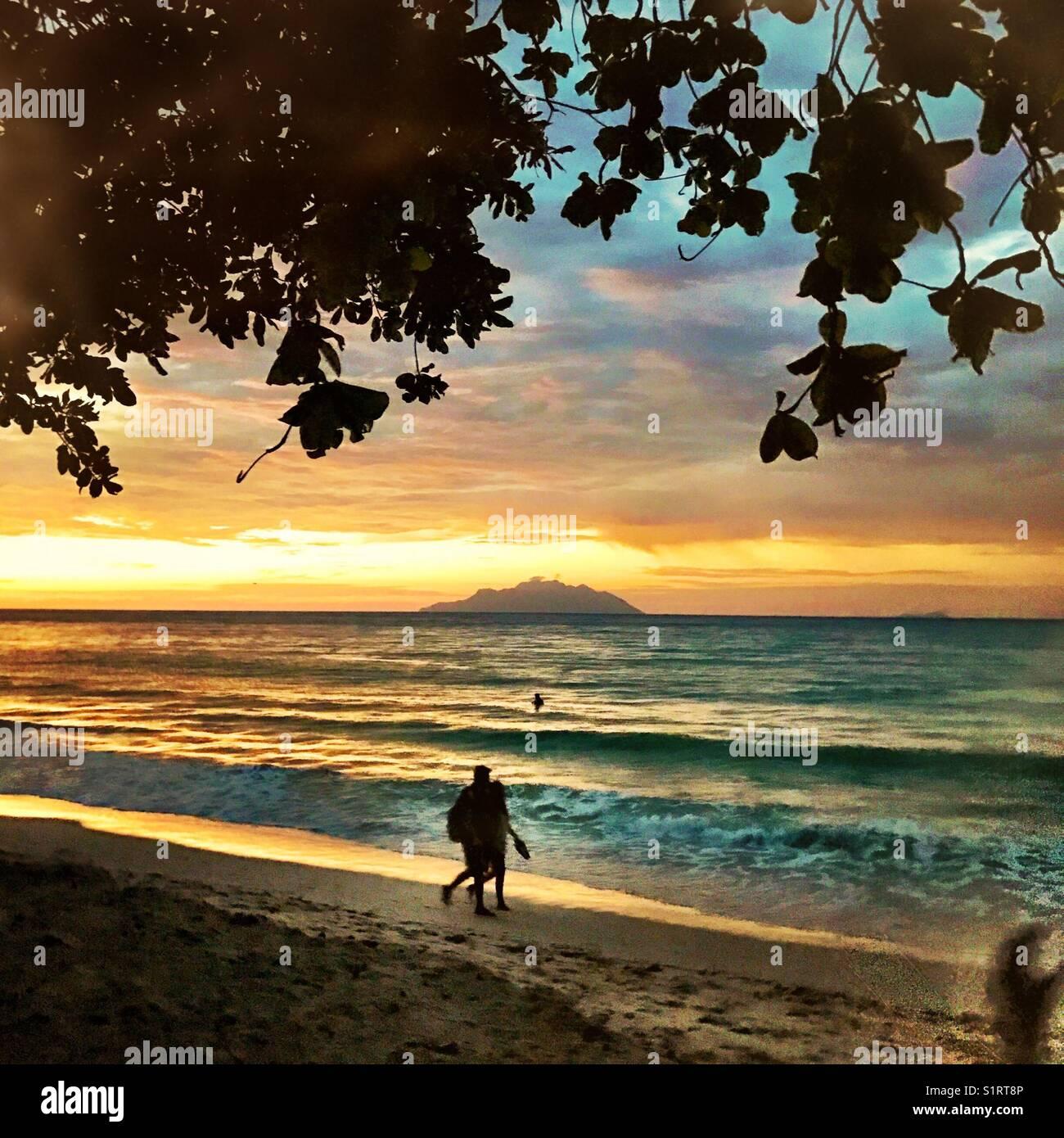 People on Seychelles beach Beau Vallon sunset Stock Photo