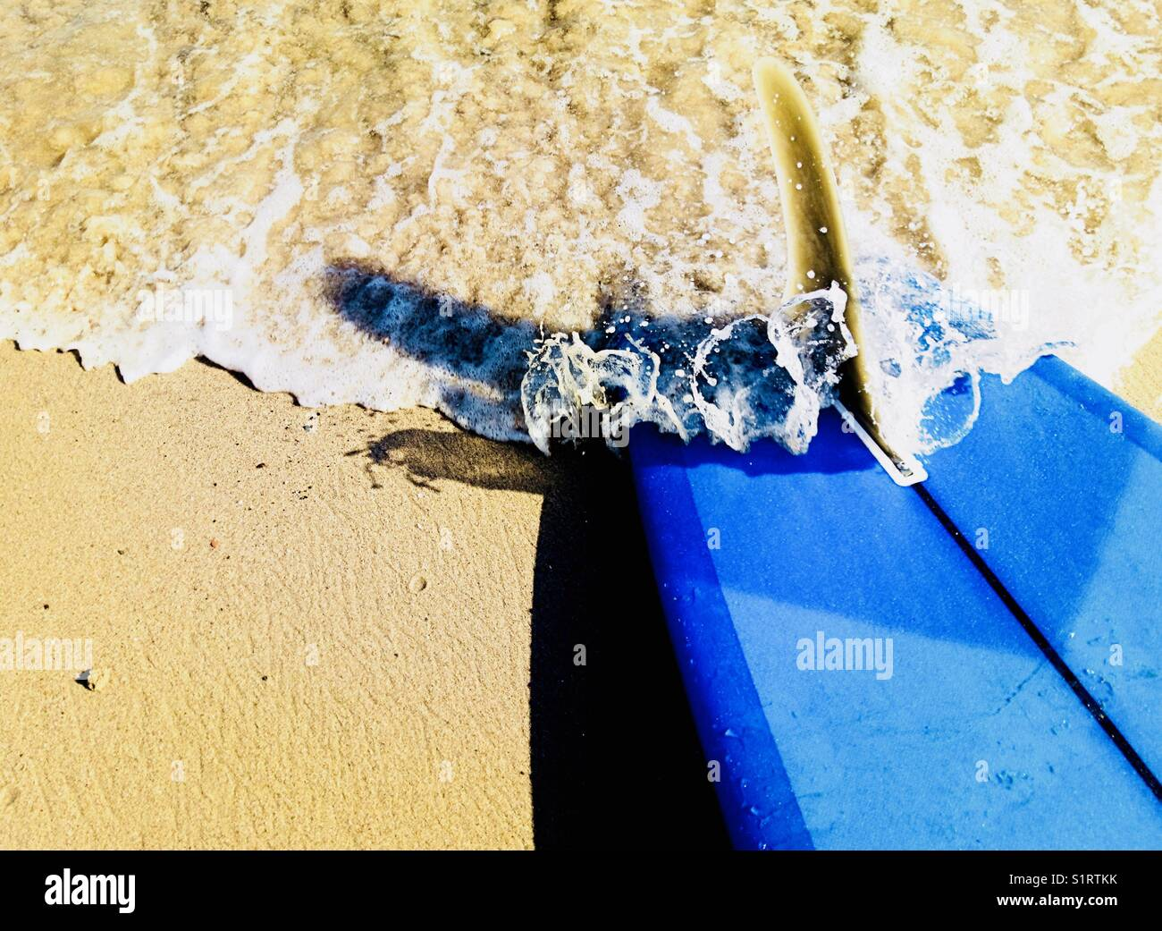 A wave rushes over a surfboard at the beach. Malibu, California USA. - Stock Image