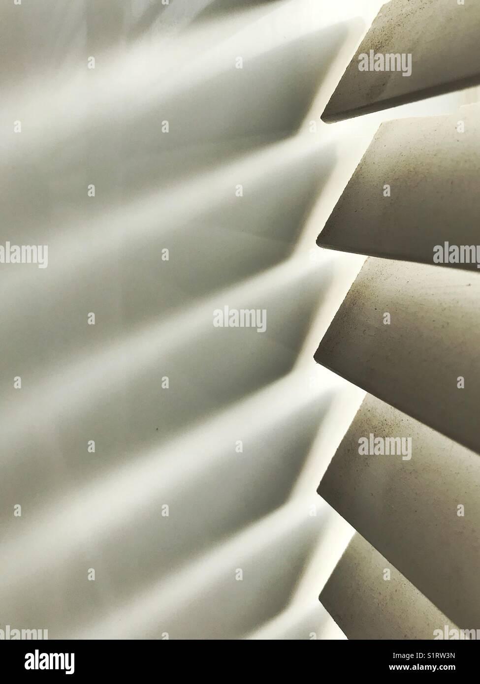 Light shining through bathroom blinds onto white tiles - Stock Image