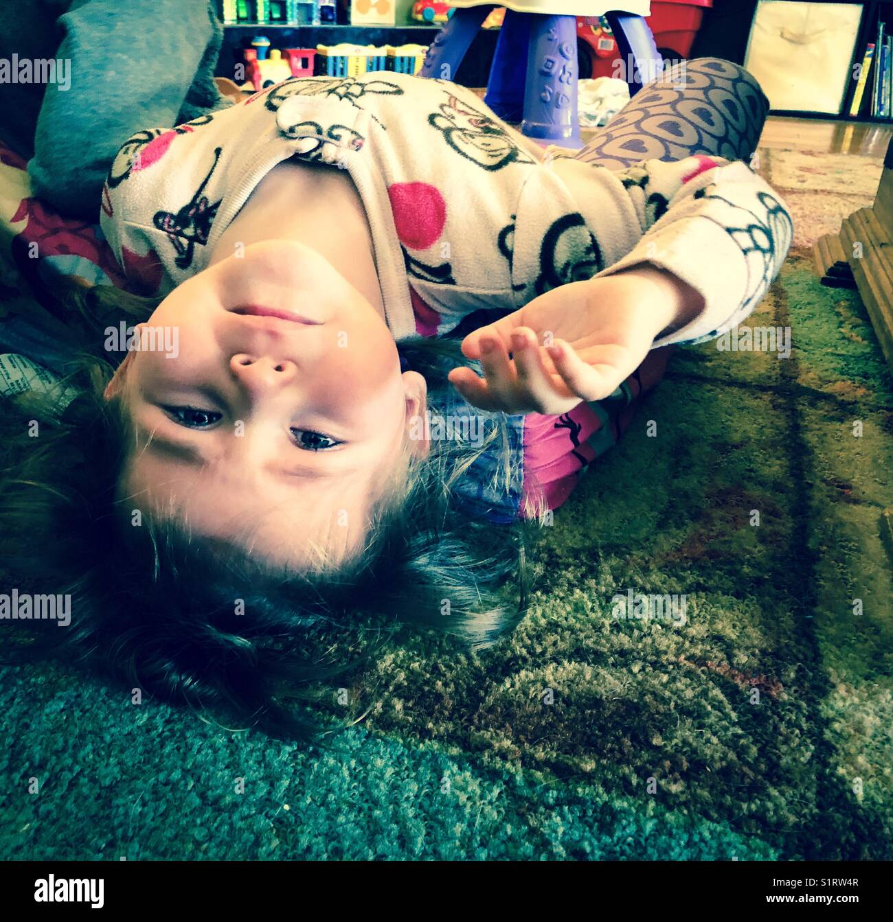 Toddler girl laying on floor looking upside down at camera with teary eyes - Stock Image