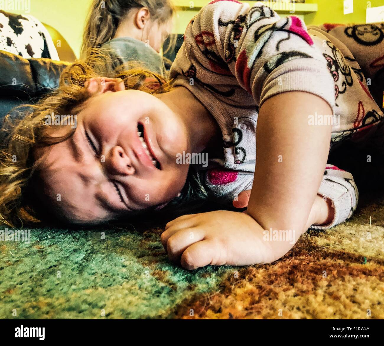 Toddler girl crying hard on carpeted floor - Stock Image