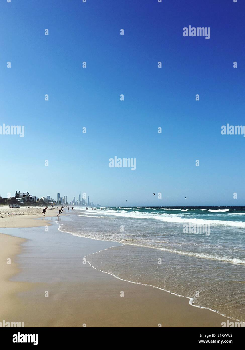 Two guys running towards the water. Miami Beach, Gold Coast, Queensland. - Stock Image