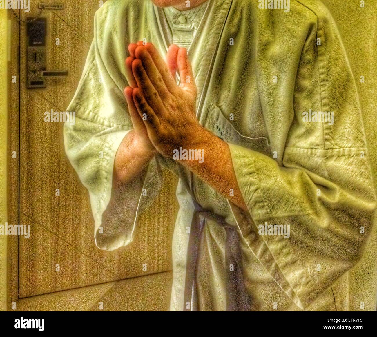 Young male adult wearing linen night robe bowing. - Stock Image