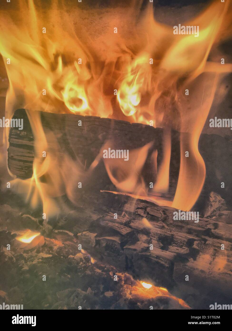 Wood burning in a fireplace. - Stock Image