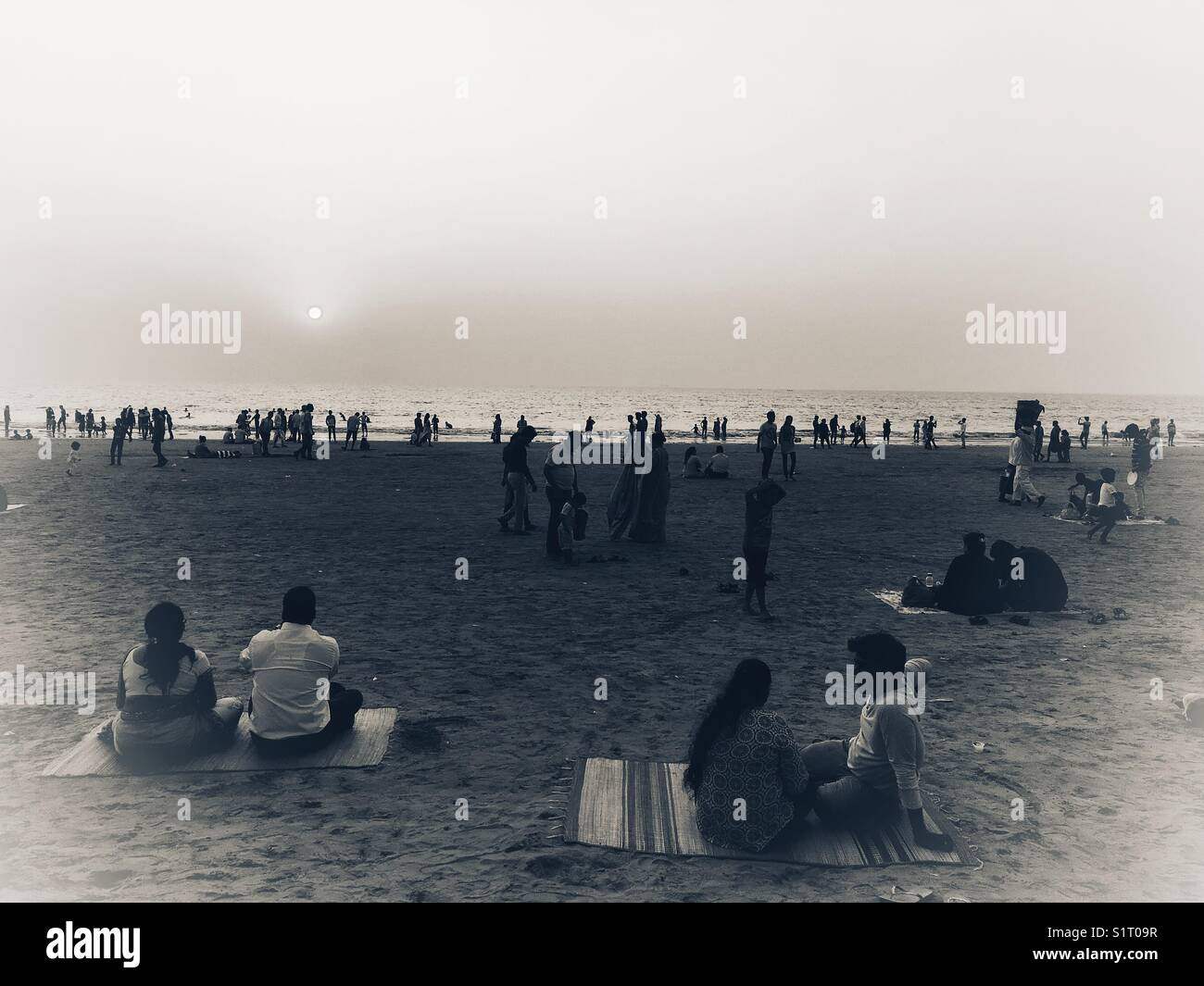 Families sits and have gala time on Juhu Beach of Mumbai. - Stock Image