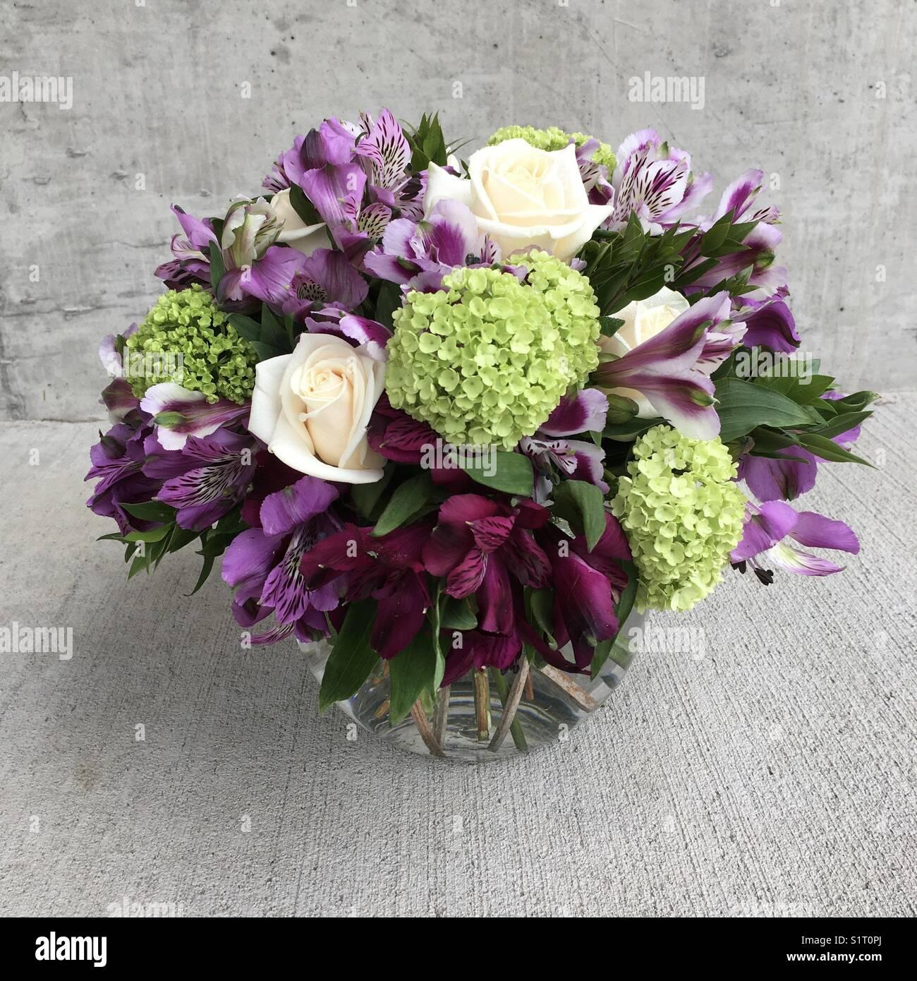 arrangement of white purple green flowers in round vase stock