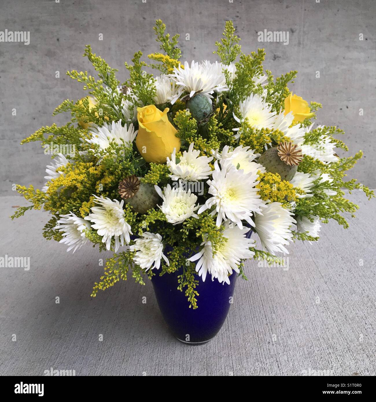 White And Yellow Floral Arrangement In Blue Vase Stock Photo
