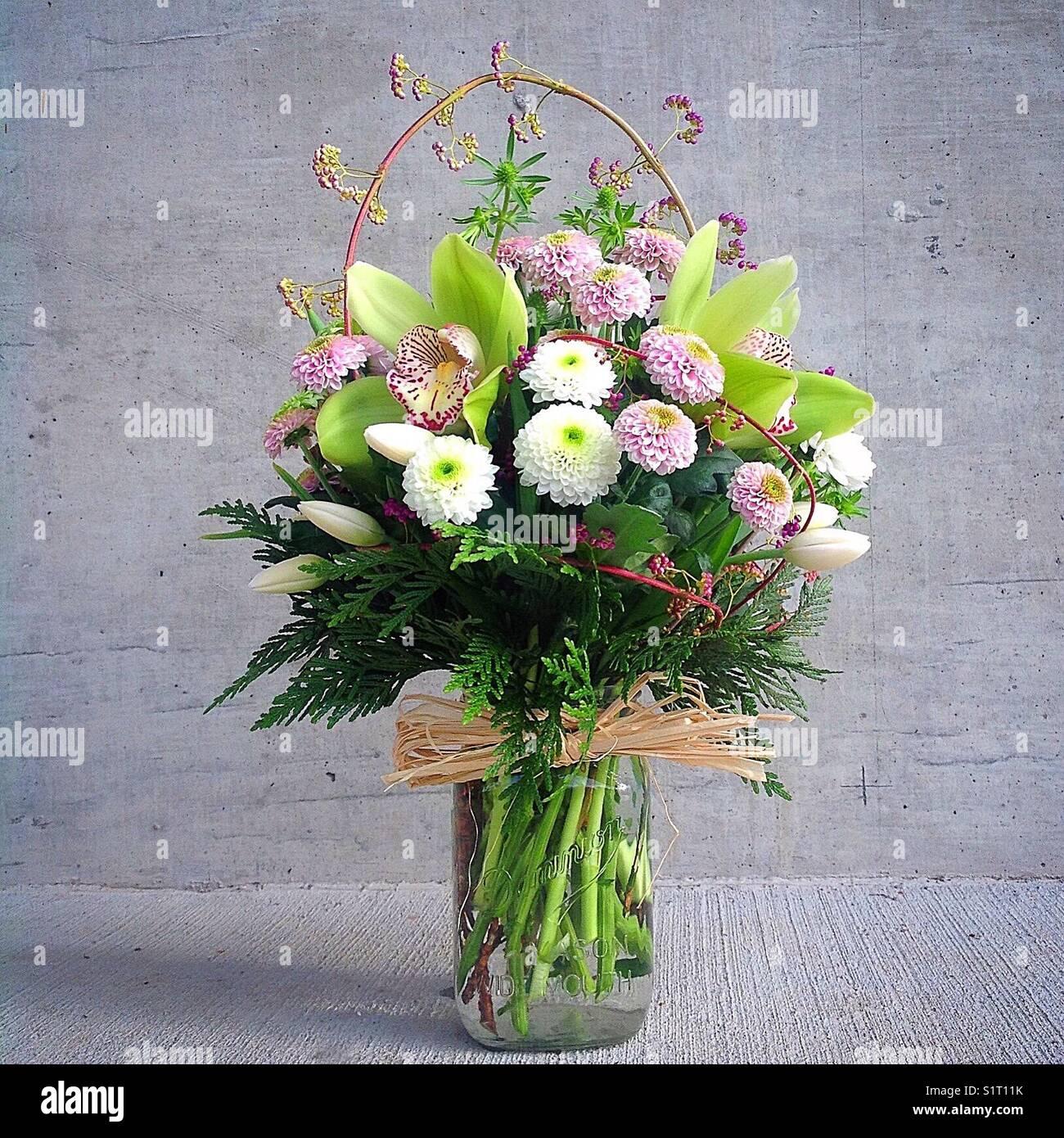 Mason jar with white, purple and green flower arrangement