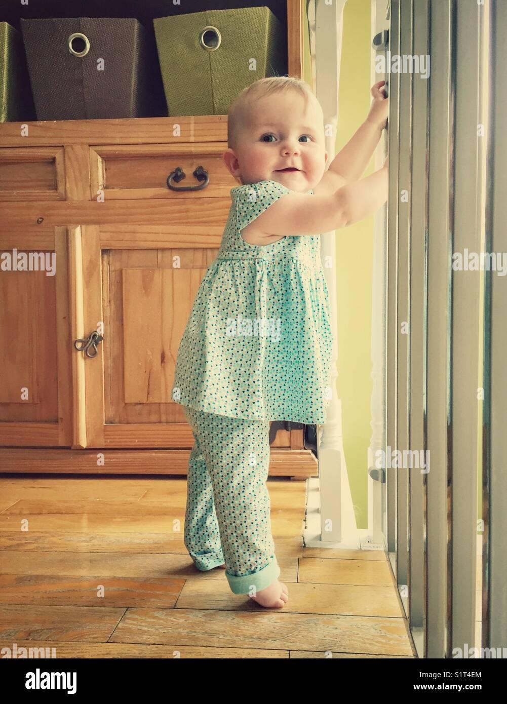 Baby girl cruising along safety gate - Stock Image