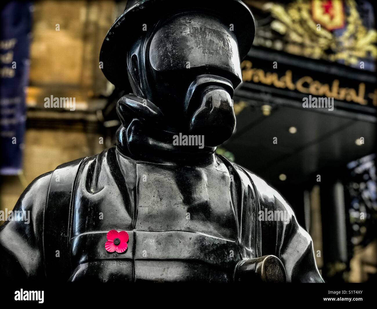 A statue at Glasgow central station with a poppy stick on his chest in memory of those who lost their lives in battle Stock Photo